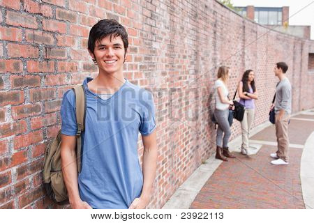 Male student posing while his friends are talking outside a building