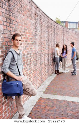 Portrait of a student leaning on a wall while his friends are talking outside a building