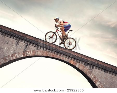 Cyclist riding bike on a bridge
