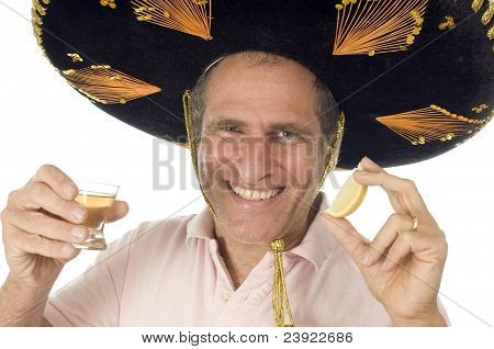 Middle Age Senior Tourist Male Wearing Mexican Somebrero Hat Drinking Tequila Shot And Lemon