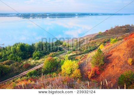 Blue river's coast with autumn trees and roads. Kama river (Ural region). Russia