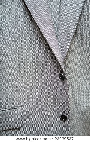 Grey single-breasted suit with buttons and pocket.