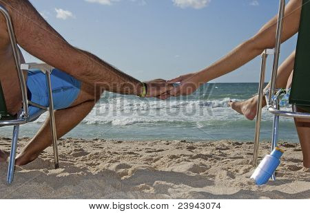 Young Couple Enjoying The Beach And Catching Sun