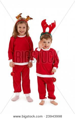 Laughing children in reindeer hair band and santa costume standing together, having christmas bulb, little boy waving.?