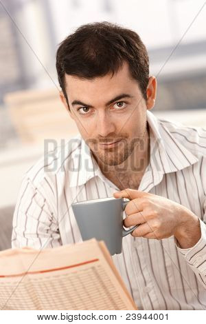 Young man reading newspaper, drinking tea at home in the morning.?