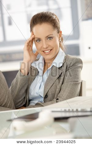 Young attractive businesswoman sitting by desk in bright office, taking a break, smiling.?