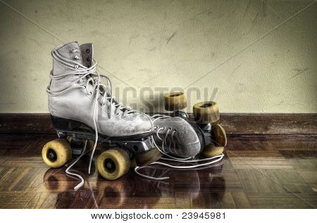 Vintage roller skates with big shoe-laces on a yellow wall background