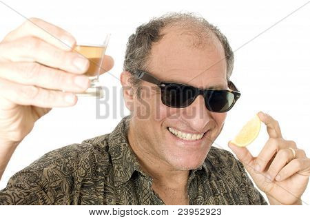 Middle Age Senior Tourist Male Sun Glasses  Drinking Tequila Shot And Lemon