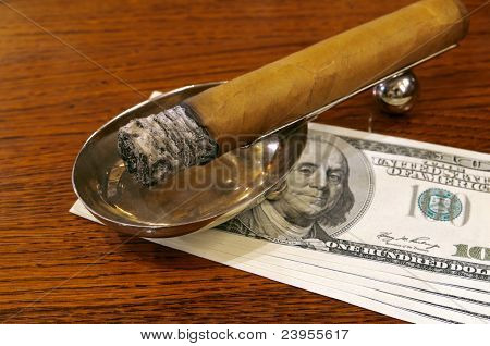 Cigar on a stand with money