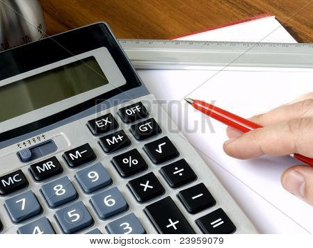 Mão com vermelho, uma caneta e uma folha de um papel deitado sobre uma mesa