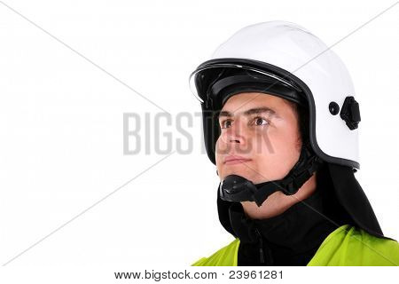 A picture of a young firefighter in a white helmet looking against white background