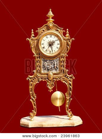 ancient vintage brass pendulum clock isolated on red
