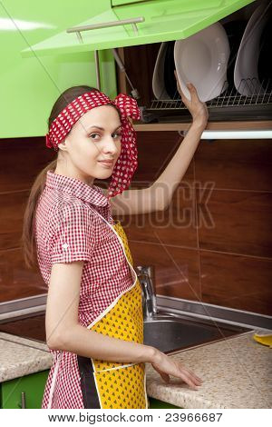 Woman in kitchen interior with clean plates