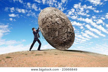 Empresario rodar una piedra gigante