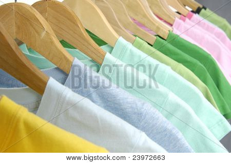 line of multi colored shirts on wooden hangers