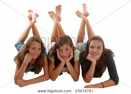 Three Teenage Girls Laying On Floor Chin In Hand