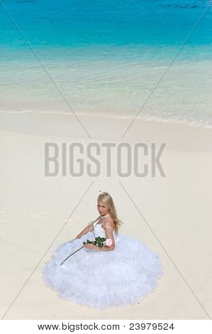 The young beautiful woman in a dress of the bride sits on sand at sea edge