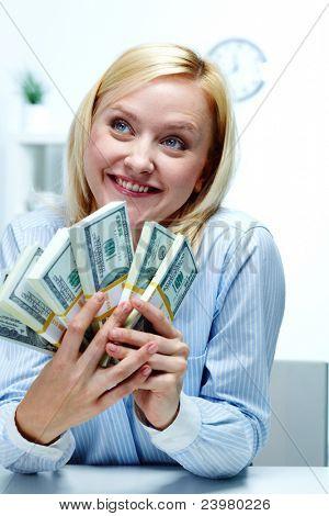Porträt einer jungen Frau holding Roll von Banknoten und genießen
