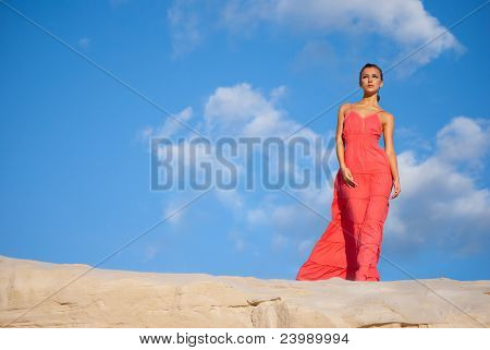 beauty woman in red dress on the desert