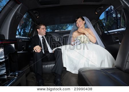 Bride and bridegroom in a luxury wedding limousine