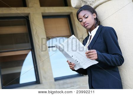 A young and pretty african american woman at college reading newspaper
