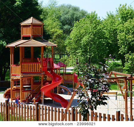 wooden castle with slide on a modern playground
