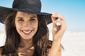 Portrait of beautiful young woman wearing summer black hat with large brim at beach. Closeup face of poster