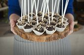 Platter Of Cake Pops With Chocolate Icing In Hands Of Waitress. Candy Bar And Catering Concept For B poster