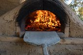 Pizzas Cooking In Stone And Cob Pizza Oven. Traditional Cooking Scene, Background poster