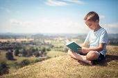 Boy sitting and relaxing on a hill reading a book in a meadow concept for education and relaxing poster
