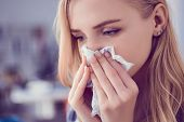 Concept Of Treatment For Allergies Or The Common Cold. Girl Blows Her Nose Into A Tissue. poster