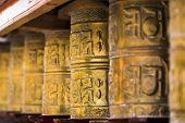 Tibetan buddhist praying wheels in Ladakh, India. Traditionally, the mantra Om Mani Padme Hum is wri poster