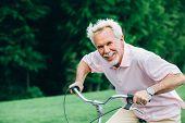 Lively Older Man Riding His Bicycle, Laughs And Enjoys Life. Senior Man On Bike, Having Fun poster