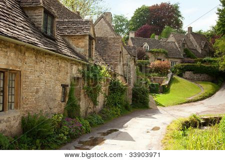 Traditional Cotswold cottages in England, UK.  after the rain. spring. Bibury is a village and civil parish in Gloucestershire, England.