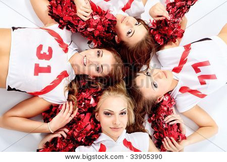 Group of professional cheerleaders posing at studio. Isolated over white.