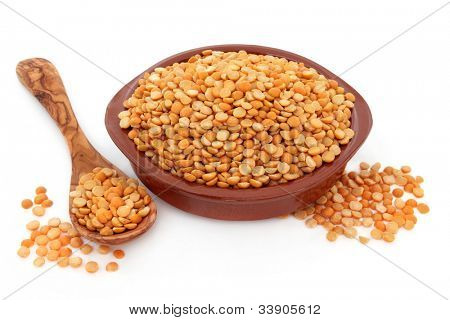 Yellow split peas in a terracotta bowl, olive wood spoon and loose over white background.