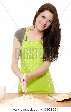 happy young woman preparing dough for baking