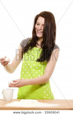 woman preparing eggs for baking with flour