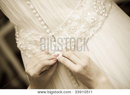 Detail of bridesmaid fixing bride's wedding dress
