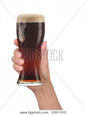 Closeup of a male hand holding up a glass of foamy dark ale over a white background. Vertical format with drip running down the side of the beer glass.