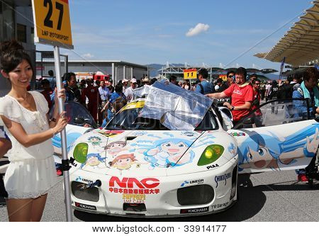 SEPANG - JUNE 10: A grid girl poses with the Ferrari F430 car of the LMP Motorsport Team on the start grid at the Autobacs SUPER GT Series Rd 3 on June 10, 2012 at the Sepang Int. Circuit, Malaysia.