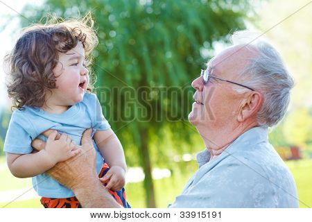 Great granddad holding  little curly baby in hands