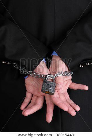 Mãos de empresário restringidas com corrente e cadeado