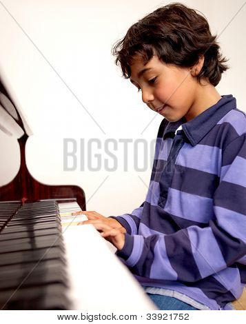 Cute boy playing the piano at home