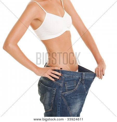 Funny woman shows her weight loss by wearing an old jeans, isolated on white background