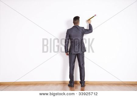 Businessman writing with a giant pencil at the white office blank wall