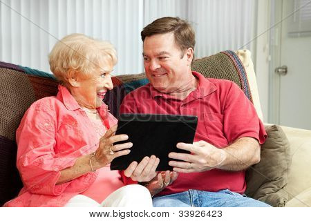 Adult man giving his mother a tablet PC and teaching her to use it.