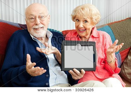 Confused senior couple holding their new tablet PC.  Blank computer screen ready for your text.