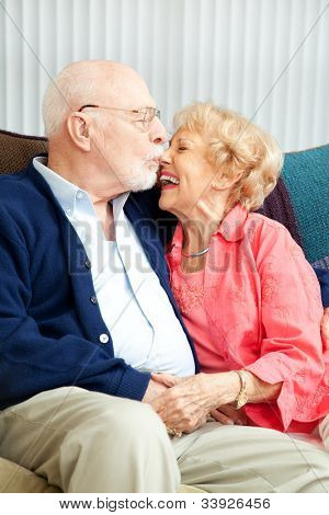 Senior couple relaxing at home, she's laughing as he kisses her nose.