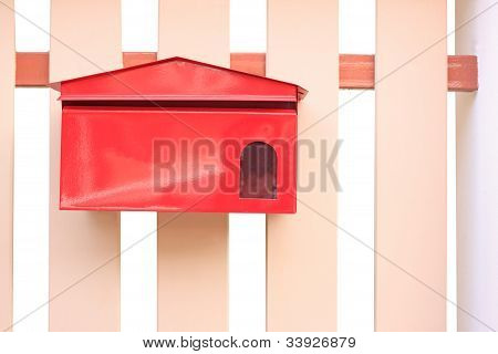 red mail box hanging on fence